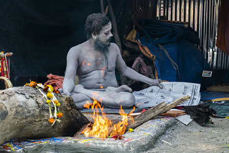 A sadhu reads a newspaper at a transit camp. Thousands of Indian Hindu pilgrims heading to the Ganga Sagar annual fair, which is held on an Island in the mouth at Sacred Ganges River from 10th Jan to 17th Jan. The babughat transit camp acts as a pit stop to break up their journey.