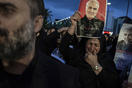 A woman crying while holding a poster of Qasem soleimani. Four days after the death of General Qasem Soleimani by the US military in Iraq, people across Iran's cities mourned and demanded a harsh revenge on the United States.