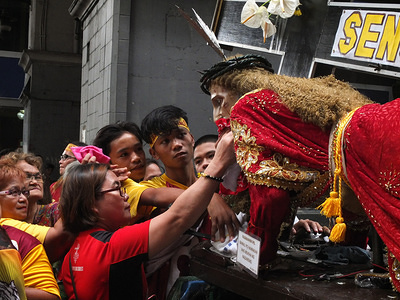 """Nazarene devotees alternatively wipe the face of the Nazarene statue during the event. Filipinos gather at Quiapo in Manila for the feast of Black Nazarene, A life-size statue of a suffering Jesus Christ fallen from the weight of the cross. Catholic devotees do """"pakaridad"""" a way of giving or sharing food to others and a long procession of the Statue."""