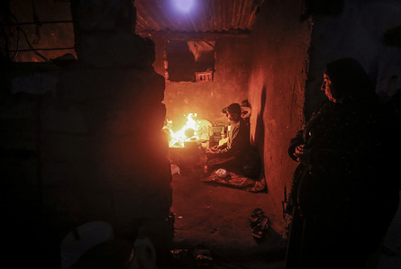 GAZA CITY, PALESTINE, JANUARY 9, 2020: A Palestinian woman warms herelf next to a fire during a cold weather spell in a slum on the outskirts of the Khan Younis refugee camp.