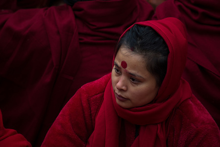 KATHMANDU, NEPAL - JANUARY 10 2020: A Nepalese Hindu devotee dressed in red looks on during the festival. Madhav Narayan festival or Swasthani Brata katha is a festival in which devotees recite holy scriptures dedicated to Hindu goddess Swasthani and Lord Shiva. Nepalese Hindu women who are unmarried pray for a good husband while married pray for the long life of their husband.