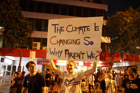 A protester holds a placard that says the climate is changing so why aren't we? during the Uni Students For Climate Justice rally in Brisbane. Uni Students For Climate Justice organised a rally through the streets of Brisbane (and in other cities) to call for better funding for fire services both state funded and volunteer, the revamping of climate policy and for the sacking of Prime Minister Scott Morrison, who has in recent weeks been criticised for his handling of the situation while many thousands of hectares have burnt in Queensland, New South Wales, Western Australia, South Australia and the Australian Capital Territory.