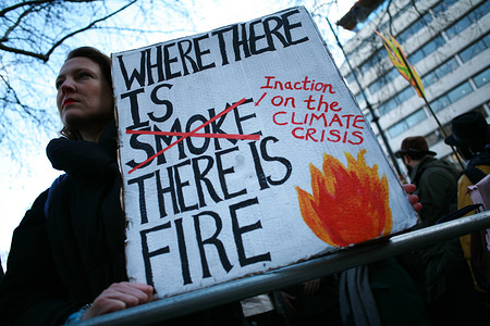 Protester holds a placard during a demonstration by members of the climate change activist movement Extinction Rebellion (XR) against Australian government's response to its ongoing bush fires outside the Australian High Commission in London. Wildfires have burned more than 12 million acres of Australian land since September last year, with the states of New South Wales and Victoria most severely affected and with the fire season still far from over. Australian Prime Minister Scott Morrison is facing intense criticism over his handling of the crisis, including his decision to go on holiday to Hawaii last month and his government's refusal to break ties with the country's powerful coal lobby. Worsening climate change is expected to exacerbate the conditions around the world that cause such devastating fires to begin.