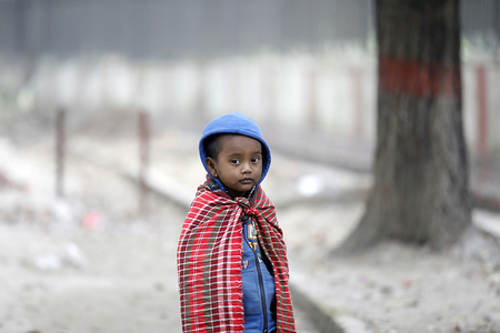 A kid poses for a photo during the cold weather in Dhaka. The colds wave continues to disrupt life across the country in Bangladesh.