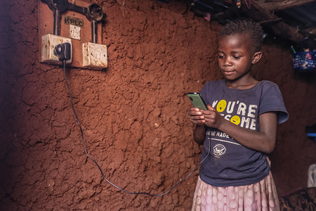 9 year old Ann, checks on her mothers phone battery charging percentage. Lack of electricity had been and is still one of the poverty and problems faced by over 2 million citizens living in Kenya's largest informal settlement Kibera Slums. It is one of the big challenges that has participated in drugging down Kenya's economic growth as not everyone can pay the energy consumption bills. In Kibera Slums, Illegal Electricity acts as one of the basic needs to most owners of small businesses operating here from early mornings till late midnights and serves most jobless youths who depend on it as their main Source of Income by renting it out illegally for 2 to 3 dollars to be able to feed their families and pay their bills. Despite the 2015 joint collaboration of the World Bank and (K.P.L.C) Kenya Power and Lighting Corporation which is Kenya's main Power distributor to come together and create cheap and fair access to electricity. By creating electric tokens and being able to provide them to few numbers of homes, not everyone prefers this method but they instead run for the poor and risky illegal supply. Most of the time residents here have been enjoying the Illegal connection of electricity but most times they are attacked by abrupt skirmishes like fire outbreak and deaths from the naked uncovered wires running from Rooftops to different corners of the houses and underground leading to death and burning down of house and loss of Properties.