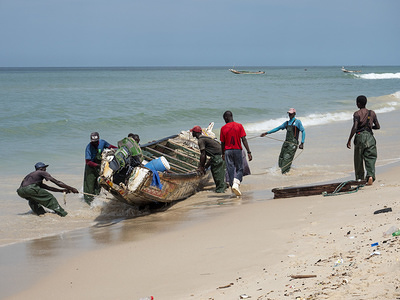 Fishermen drag their boat on the shores of the ocean at the fishermen quarter Guet Ndar in Saint Louis. Saint Louis in Senegal is one of the places on Earth the most affected by the climate change. Because of rising of the ocean level, thousands of people were forced to leave their homes.