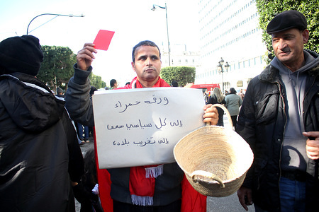 A man holding a basket with a red card during the anniversary. Tunisians gather at the Tunisian General Labour Union (UGTT) building for the 9th Anniversary of ousting President Zine El Abidine Ben Ali.