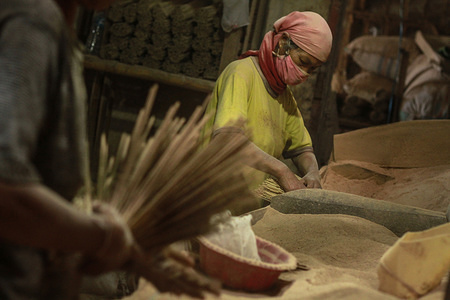 MALANG, INDONESIA - JANUARY 16 2020: Traditional incense in the making. As the Chinese New Year approaches, incense demand is increasing and workers who use improvised masks have to go an extra mile.