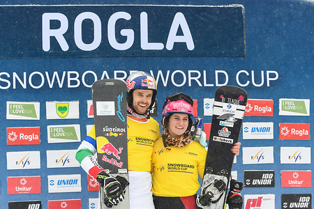 World Cup leaders Roland Fischnaller of Italy and Ramona Hofmeister of Germany pose on the podium after the FIS World cup Parallel Giant Slalom in Rogla.