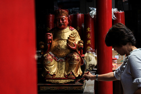 A woman brushes a statue during the celebration at Dharma Ramsi temple in Bandung. Cleaning the statues of gods is one of the traditions Chinese citizens to welcome Chinese New Year.