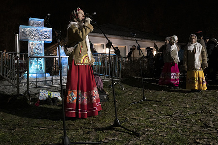 A woman dressed in a traditional costume sings during the celebration. The annual commemoration of the baptism of Jesus Christ in the Jordan River is celebrated by thousands of Russian Orthodox believers as part of celebrations for the Epiphany fest. Despite the unusual warm temperature that hampered the formation of a strong ice cover of lakes and rivers, several stations had been prepared in the urban area in Moscow, as the one in the Sokolniki Park, for believers who wanted to take the traditional plunge that is considered an act for washing out one's sins.