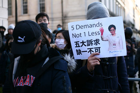 A demonstrator holds a placard featuring a picture of Hong Kong Chief Executive, Carrie Lam during the protest. Activists rally in solidarity with the pro-democracy movement in Hong Kong and in protest at China's treatment of its Tibetan and Uighur peoples at a demonstration for all three causes outside the Chinese Embassy in London. In its newly-released 'World Report 2020', New York-based research and advocacy NGO Human Rights Watch last week singled-out 'deepening repression' by Chinese authorities during 2019, including of religious freedoms in Tibet and in the Uighur homeland of Xinjiang, as the defining feature of what was the 70th anniversary year of the Chinese Communist Party.