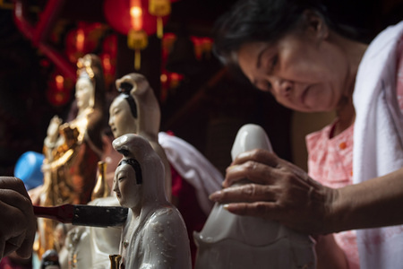 A woman cleans a statue during the celebration at Dhanagun Temple in Bogor. Cleaning the statues of gods is one of the traditions Chinese citizens to welcome Chinese New Year.