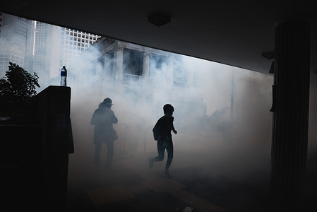 Two woman run through clouds of tear gas during the demonstration. Thousands of pro-democracy protesters attended an anti-communism rally, the rally ended 3 hours earlier due to police firing tear gas into protesters who eventually dispersed to multiple locations around the city and continued to protest.