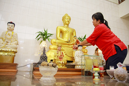 MEULABOH, ACEH, INDONESIA - JANUARY 21, 2020: A woman cleans a buddhas statue during the celebration at Sakyamuni Temple in Meulaboh. Cleaning the statues of gods is one of the traditions Chinese citizens do to welcome Chinese New Year.