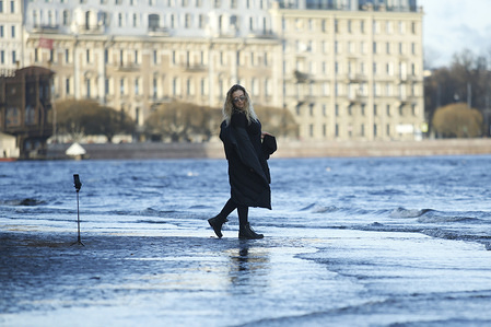 A woman poses for a photo at the Neva embankments as water level rises along the Neva River in Saint Petersburg, Russia.