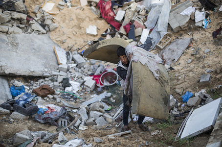 Muhammad Hammouda Abu Amra, 19, extracts a mattress from the ruins of their destroyed home. The Abu Umrah family that consists of 19 individuals lost their five-storied house after an Israeli raid on Gaza on November 13, 2019.