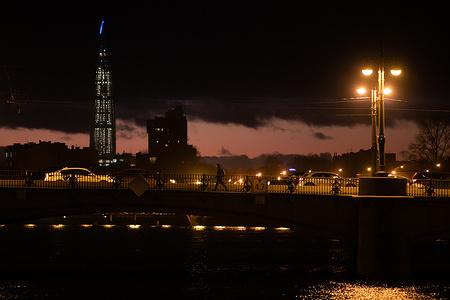 People walk along the Ushakovsky Bridge during sunset.