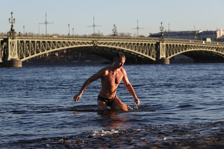 A man gets out of the Neva river during sunny day.  Temperature dropped to minus 2º degrees.