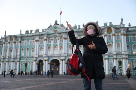 A Chinese tourist wearing a medical protection mask is seen near Hermitage at Dvortsovaya (Palace) square. All passenger flights to Moscow and St. Petersburg from China's Wuhan pass checking for coronavirus symptoms. The outbreak of coronavirus has so far claimed 26 lives and infected more than 800 others, according to media reports
