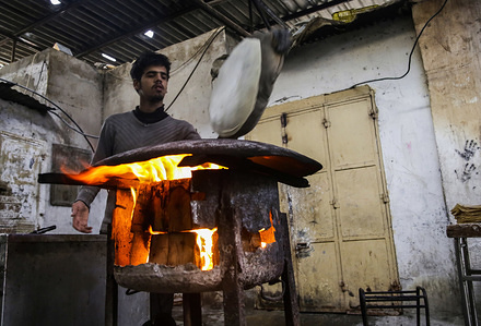 """A Palestinian seller prepares traditional bread known as """"Saj"""" in Gaza City."""