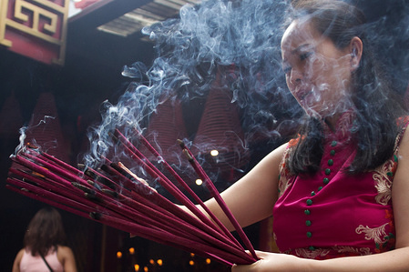 A woman burns incense while praying during the Chinese New Year celebration at a Temple in Jakarta.