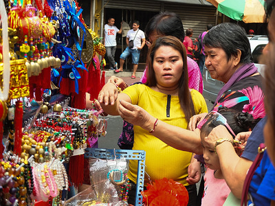 """A woman seen choosing a lucky charm ornament that she will buy for the New year celebration. Filipinos and Filipino-Chinese celebrate Chinese New Year by visiting Binondo to enjoy dragon dances, fireworks and shopped Chinese foods such as much-loved """"Tikoy"""". They also buy rounded fruits and lucky charms for luck and prosperity."""