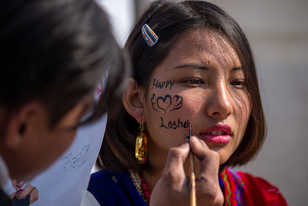 An artist face paints a woman during the celebration. Tamang community celebrates Sonam Losar or New Year which occurs at the same time with the Chinese and Mongolian New Year.