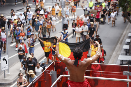 An indigenous protester applauds the crowd as they march towards Musgrave Park during the rally. Indigenous Yuggera and Turrbal people organized a rally in Brisbane (Meanjin in the indigenous language) to protest the Australia Day holiday on the 26th January, a date seen as synonymous with the beginning of British colonial rule and oppression of Aboriginal people. They called for a change to the date and discussed themes such as fighting against racial injustice and remembrance of the Stolen Generations and Aboriginal sovereignty.