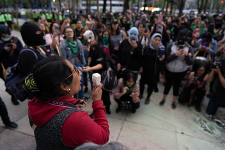 Mother to a murdered female activist speaks to the women during the march. Hundreds of women attended the first feminist march of 2020 in Mexico City surrounded by hundreds of female police officers.  The women used paint, fire to threaten police and men who came close to them. The women were campaigning for change in Mexico. The march was for female activists who had been assassinated, specifically Isabel Cabanillas and Yunuen L—pez S‡nchez.