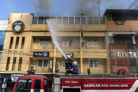 Firefighters put out fires on the roof of the burning A&W fast food restaurant in Banda Aceh. The incident allegedly caused by fire that originated from a warehouse near a fast food restaurant.