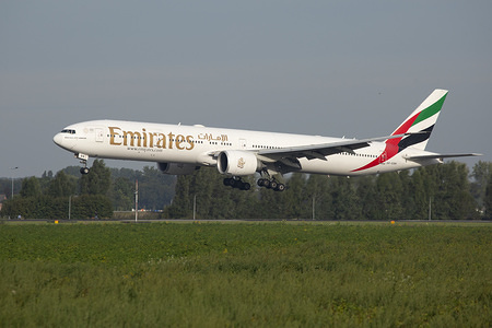 Emirates, Boeing 777-300ER commercial airplane lands at Amsterdam Schiphol AMS airport in the Netherlands.  The Dubai based airline, UAE B777 is a wide body extended range aircraft with registration A6-EBM and 2x large GE90 jet engines.