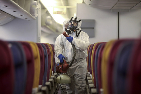 SAMUT PRAKAN, THAILAND - JANUARY 28, 2020: Crew member in a protective suit and mask spraying during the disinfection process. Thai Airways International spray disinfectant on passenger seats all plane following a risky corona virus infection. Thailand has detected 14 cases, Thai health officials are stepping up monitoring and inspection. The virus has so far killed at least 106 people an outbreak which began in the Chinese city of Wuhan.