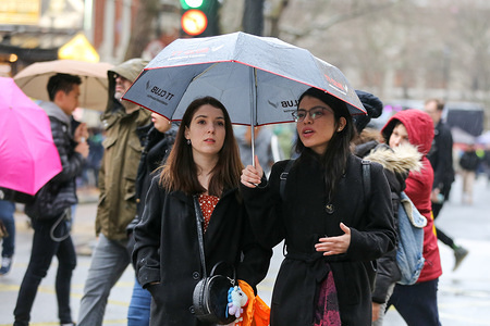 Women share an umbrella during the rainfall in central London.