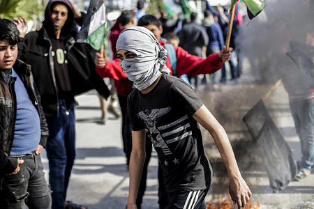 Palestinian man with a face mask during the demonstration. Palestinians demonstrate against US President Donald Trump's expected Middle East peace plan proposal.
