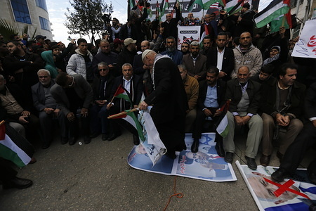 An elderly Palestinian protester steps on posters depicting US President, Donald Trump and Benjamin Netanyahu during a protest against the US peace plan about the Middle East in Rafah.