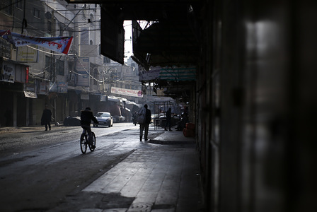 Palestinians walk past closed shops during the general strike to stage a protest against the US peace plan in Gaza City.