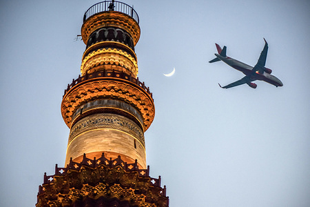 A passenger aircraft flies over the historic Qutub Minar in Delhi. Qutub Minar, a UNESCO World Heritage Site, is the tallest minaret in India. The Qutub Minar was built in the early 13th century a few kilometers south of Delhi.