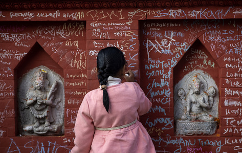 A kid writes on the wall of Swaraswati temple during the Shree Panchami festival. On Shree Panchami day, people especially children go to the temple for their first writing and reading lessons in belief that goddess Saraswati, the goddess of knowledge, wisdom and learning will help them excel in education.