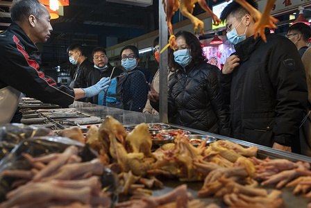 Customers using face masks buy chicken meat at a food market in Hong Kong. Since the start of the coronavirus outbreak, the death toll now stands at 170, infected people  more than 7,700 and 12,000 more under observation.