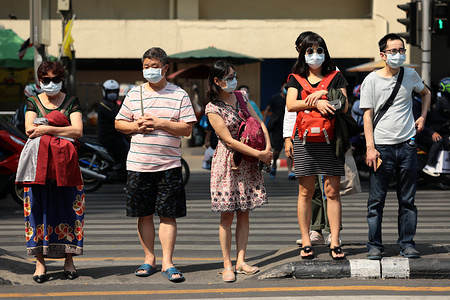 Chinese tourists wearing protective face masks stand near the Erawan shrine in Bangkok. Thai health officials are stepping up monitoring and inspection for coronavirus. Thailand has detected 14 cases. The virus has so far killed at least 170 people an outbreak which began in the Chinese city of Wuhan.