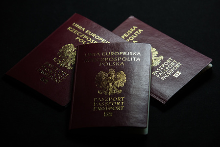 In this photo illustration burgundy red biometric Polish passports seen displayed.