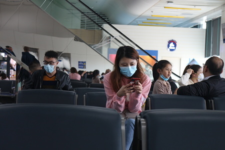 A woman wearing a face mask as a precaution to the outbreak of Coronavirus looks at her phone at the departure terminal of Zhuhai airport. The World Health Organisation (W.H.O) has declared the epidemic an international public health emergency.