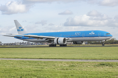A KLM Royal Dutch Airlines Boeing 777-300 wide-body aircraft lands at Amsterdam Schiphol AMS EHAM Airport in the Netherlands at Polderbaan runway.  The airplane has ETOPS certification for transatlantic flight.
