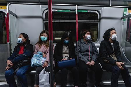 MTR passengers wear surgical face masks on their commute. Citizens throughout Hong Kong are wearing face masks to prevent against the Coronavirus. Originating in Wuhan, China, the virus has spread beyond China's borders into Hong Kong as well as other countries abroad.