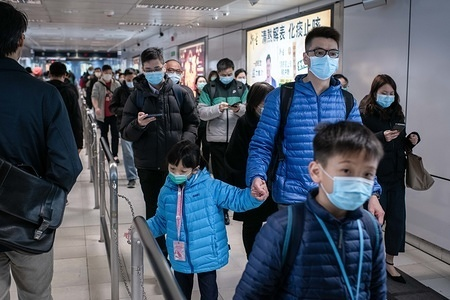Commuters wear masks while crossing Kowloon Tong MTR  Station. The World Health Organization called a global health emergency, reversing earlier decision on coronavirus outbreak. So far there are 13 confirmed cases of the coronavirus in Hong Kong, while the total confirmed cases has jumped to 14,549 and the death toll has risen to 305.