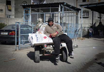 A man sits on his donkey as people receive food aid from United Nations Relief and Works Agency (UNRWA) at a distribution centre in Khan Yunis camp for Palestinian refugees in the southern Gaza Strip.