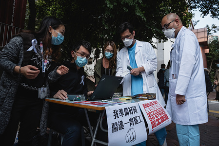 Doctors register for the medical workers strike in support of the Hong Kong-mainland border closure. Hundreds of medical workers participated in a strike in support of the complete closure of the Hong Kong - Mainland China border. The strike is potential a weeklong event if the government fails to address the Workers' Union concerns over the spread of the 2019 Coronavirus from mainland China into Hong Kong. Medical workers registered their participation in the strike with the union and raised various placards.