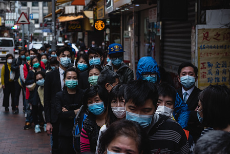 Residents in a queue around the block wait for a shipment of surgical masks to arrive at a nearby department store. Hundreds of Hong Kong residents lined up for hours in anticipation of a surgical mask delivery at a local department store. Customers were given tickets in order of arrival to guarantee their purchase of masks.