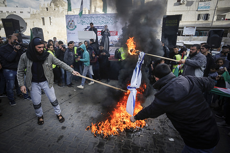 Palestinian protesters burn Israeli flags during a demonstration against US President Donald Trump's proposal for peace in the Middle East in the southern Gaza Strip.